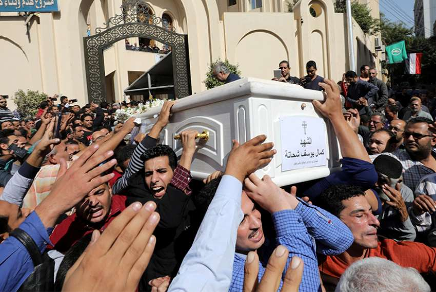 Egyptian Christians carry the casket of a victim during a Nov. 3 funeral Mass outside Prince Tadros Orthodox Church in Minya for a group of pilgrims killed by gunmen as they headed to a monastery Nov. 2.
