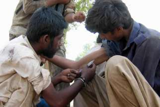A Pakistani man injects a heroin-filled syringe into a man in 2011 on the streets in Multan. Pope Francis has requested a special study session at the Vatican to look at how to solve the growing problem of drug abuse, especially narcotics.