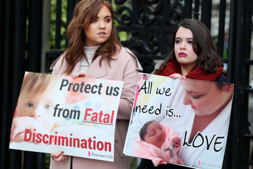 "Pro-life supporters are seen in a 2019 file photo holding signs outside the High Court in Belfast, Northern Ireland. On June 2, 2020, politicians in Northern Ireland rejected an ""extreme"" new abortion law imposed on the province from Parliament in London."