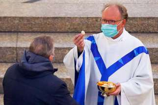 A priest wearing a protective face mask gives holy Communion to a man May 1, 2020, in a Catholic church in Kevelaer, Germany, during the first public Mass in the city since churches were closed because of the coronavirus pandemic.