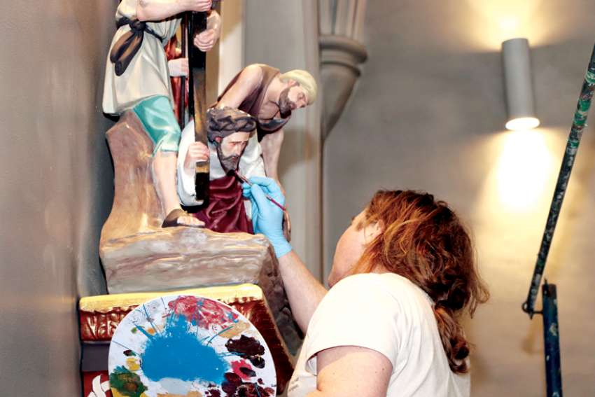 An artist puts his brush to work in restoring the statues of the cathedral in St. Catharines, Ont. The church celebrates 175 years in 2020.