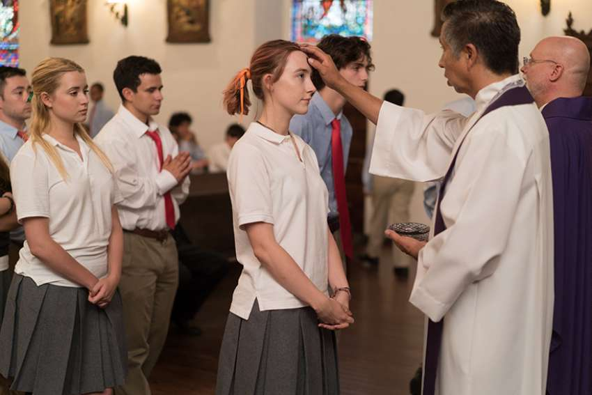 Fr. Paul Keller vested in purple applies ash on a young man's forehead during the Ash Wednesday scene in Lady Bird.