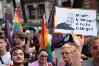 "People in Warsaw, Poland, gather outside the apostolic nunciature Aug. 7, 2019, to demand the resignation of Archbishop Marek Jedraszewski of Krakow. The protesters were upset that the archbishop had likened the LGBTQ community and the rainbow flag to a ""communist plague."" The placard reads ""Love of a neighbor? What's this?"""