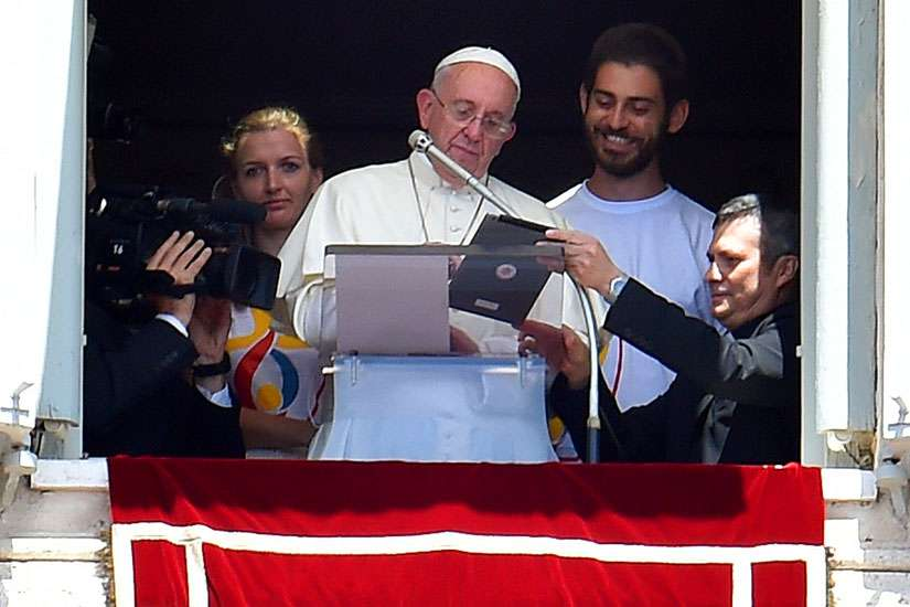 Pope Francis is flanked by two Polish youths as he uses a tablet to officially open online registration for World Youth Day 2016 in Poland.