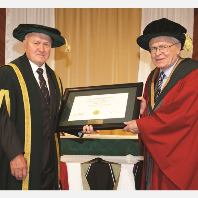 St. Jerome's University chancellor James Beingessner, left, presents an honorary doctorate to Douglas Roche June 14 at the school's convocation.