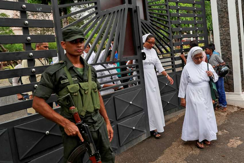 A soldier keeps guard as nuns walk out of St. Sebastian Church in Negombo, Sri Lanka, April 30, 2019. Catholic leaders canceled Sunday Masses as Sri Lanka's churches remained closed for a second week for fear of new terrorist attacks after the Easter Sunday suicide bombings that killed more than 250 people.
