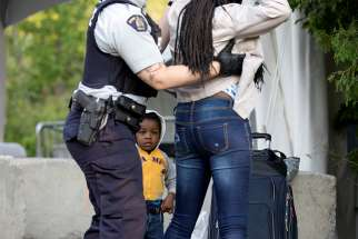 Two-year-old Evanston, whose family stated they are from Haiti, watches as a Royal Canadian Mounted Police officer pats down his mother before the two cross the U.S.-Canada into Quebec Aug. 29, 2018.