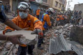 Nepalese military personnel remove debris in Kathmandu, Nepal, in search for survivors after an earthquake struck May 12. The magnitude-7.3 quake hit a remote mountainous region of Nepal that day, killing at least 19 people, triggering landslides and top pling buildings less than three weeks after the country was hit by its worst quake in decades.