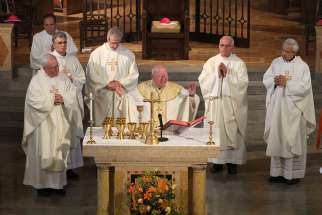 Bishop William F. Murphy of Rockville Centre, N.Y., and other bishops celebrate Mass facing the audience.