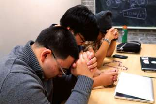 Members of Ryerson University Catholic Students' Association close their weekly meeting at the university's library with a prayer from the Exodus 90 program. Front to back are Ian Beveridge, Judel Villardo and James Delos Reyes.