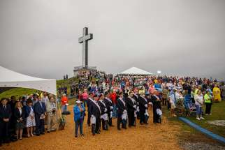 People stand near a 60-foot illuminated cross Aug. 12 at Holy Land USA, a former theme park in Waterbury, Conn., during a Mass honoring sainthood candidate Michael McGivney, founder of the Knights of Columbus and a native of Waterbury.
