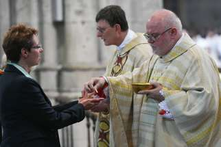 Cardinal Rainer Maria Woelki of Cologne, Germany, and Cardinal Reinhard Marx of Munich and Freising distribute Communion during Cardinal Woelki's installation Mass at the cathedral in Cologne Sept. 20, 2014.