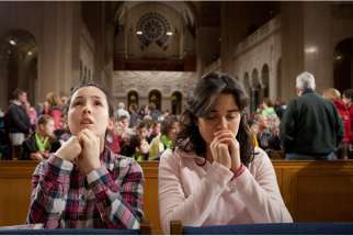 Regina Trovino and Daniela Haddad pray before the opening Mass of the National Prayer Vigil for Life at the Basilica of the National Shrine of the Immaculate Conception in Washington Jan. 24.