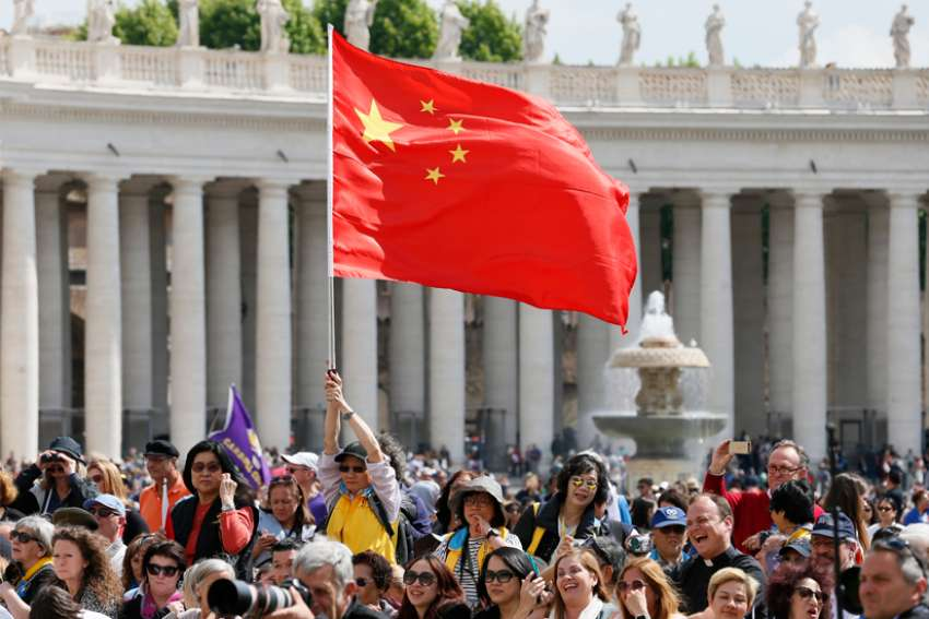 A man waves China's flag as Pope Francis leads his general audience in St. Peter's Square at the Vatican.