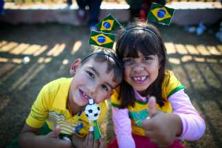 Young Brazilian fans pose for a photo outside the Arena Corinthians stadium in Sao Paulo June 11. At the Vatican, Pope Francis told fans, players and organizers the World Cup should be a celebration of solidarity and peace.