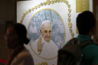 Filipinos walk past a picture of Pope Francis Nov. 20 at a museum dedicated to the pope inside a Manila cathedral where he is scheduled to celebrate Mass during his Jan. 15-19 trip to the Philippines. Philippine church officials say pope's visit will bri ng healing to the country, which was devastated by a 2013 typhoon.