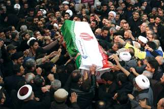 Mourners touch the casket of Iranian Maj. Gen. Qassem Soleimani during his funeral procession in Tehran Jan. 6, three days after he was killed in a U.S. drone airstrike.