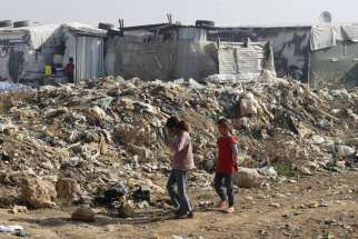 Syrian girls walk near garbage inside an informal refugee camp in Zahle, Lebanon. Lebanon continues to bear the brunt of absorbing massive numbers of refugees.