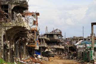 A military truck maneuvers next to destroyed buildings in the war-torn city of Marawi, Philippines. There will be no Holy Week observance this year in Marawi almost a year after extremist gunmen occupied the southern Philippine city.