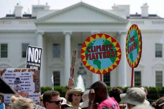 "Protesters carry signs during the People's Climate March April 29 outside the White House in Washington. Donald Trump announced June 1 his decision ""not to honour the U.S. commitment"" to the Paris climate agreement."