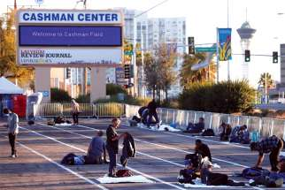 Homeless people settle in at a Las Vegas parking lot.