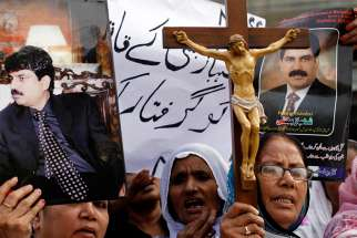 Christian women hold pictures of Shahbaz Bhatti, the slain Pakistani minister of minorities, as they demand a sentence for his killers during a protest in Karachi, Pakistan, April 6, 2011.