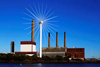 A wind turbine turns in front of a fossil fuel power plant in Charlestown, Mass., in this 2013 file photo.