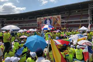 World Youth Day volunteers shield themselves from the afternoon sun while listening to the Pope's address in Panama Jan. 27.