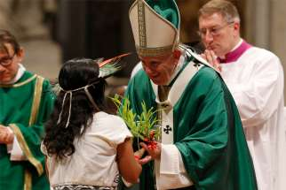 Pope Francis accepts a plant during the offertory as he celebrates the concluding Mass of the Synod of Bishops for the Amazon at the Vatican Oct. 27, 2019.