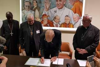 Cardinal Oswald Gracias of Mumbai, India, president of the Federation of Asian Bishops' Conferences, signs a joint statement Oct. 26 at the Vatican's Sala Marconi calling on the international community to take immediate action against climate change. Also pictured in the signing are Archbishop Gabriel Mbilingi of Lubango, president of the Symposium of Episcopal Conferences of Africa and Madagascar, left, Cardinal Jose Luis Lacunza Maestrojuan of David, Panama, president of Latin American bishops' council's economic committee, Archbishop Jean-Claude Hollerich, president of the Commission of the Bishops' Conferences of the European Union, right.