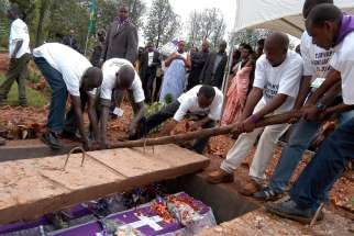 olunteers are seen in 2005 burying the remains of victims of the 1994 genocide in Murambi, Rwanda. A Rwandan government commission has criticized the dismissal of genocide charges against a Catholic priest who fled to France after the 1994 mass killing of the African country's Tutsi inhabitants.