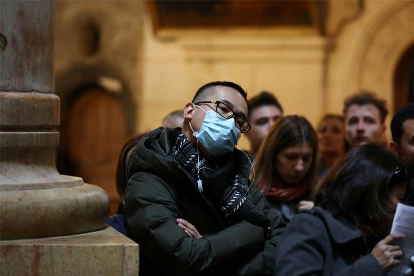A man wears a protective mask during Mass at the Church of the Holy Sepulcher in Jerusalem's Old City March 1, 2020. With Holy Week celebrations closed to the public due to the coronavirus pandemic, Pope Francis postponed the traditional Good Friday collection for the Holy Land to September, the Vatican announced April 2.