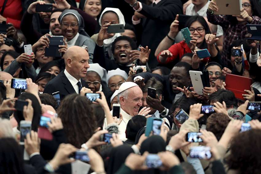 People take pictures with mobile phones and tablets as Pope Francis arrives at the Vatican on Nov. 21, 2015.