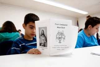 Children read about first Communion during a preparation class.