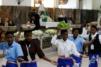 Women carry baskets of food on their heads as they dance during Pope Francis' meeting with bishops, priests, religious, seminarians and catechists at the Cathedral of Our Lady of the Immaculate Conception in Maputo, Mozambique, Sept. 5, 2019.