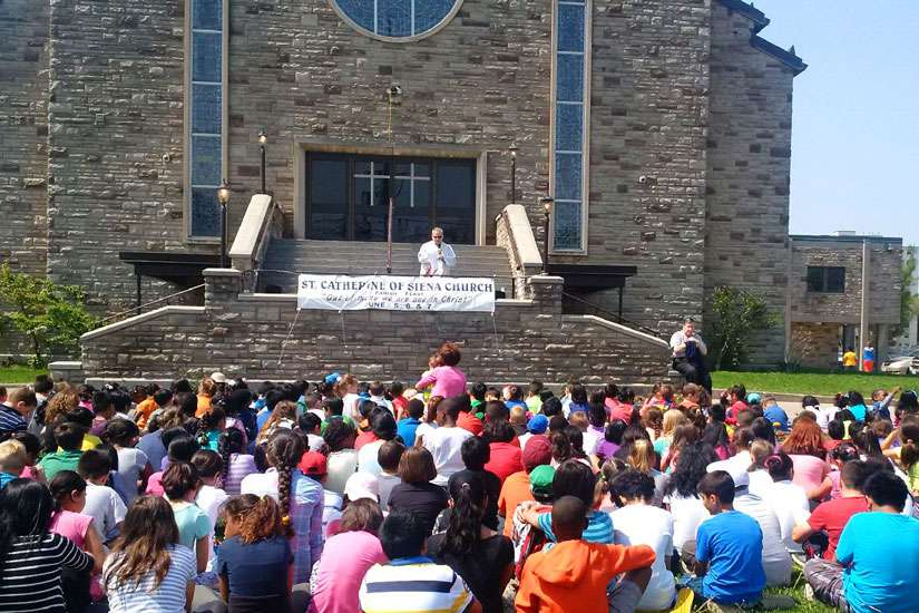 Students and staff of St. Catherine of Siena Separate School gathered at the church for a prayer service led by Fr. Camillo Lando May 28. The St. Catherine school has pledged to pay for a new statue of the Sacred Heart of Jesus following a third attack of vandalism on the church grounds May 20.