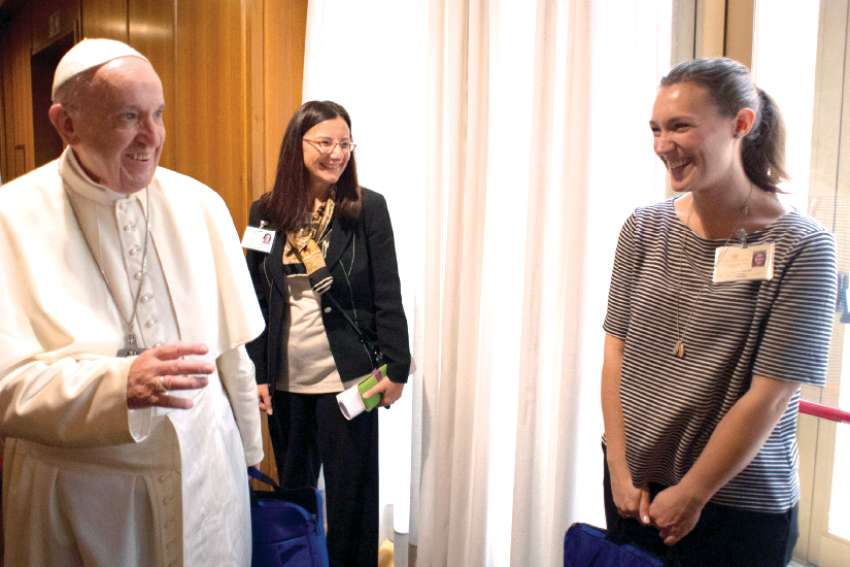 Pope Francis greets Emilie Callan, right, a synod delegate from Canada, during a session of the Synod of Bishops on young people, the faith and vocational discernment at the Vatican Oct. 11.