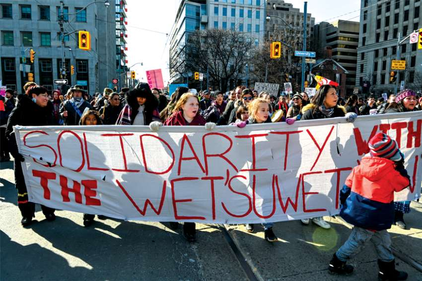 Solidarity banner leads thousands through downtown Toronto on Feb. 22 in a show of support for the Indigenous people protesting a B.C. gas pipeline.