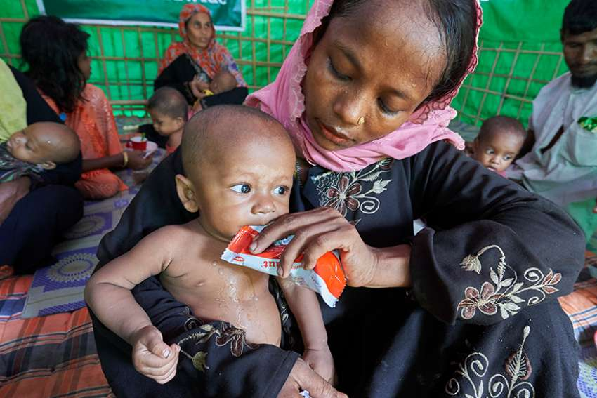 A woman from Myanmar feeds her child in a U.N. clinic for severely malnourished Rohingya children Oct. 28 in the Balukhali Refugee Camp near Cox's Bazar, Bangladesh. More than 600,000 Rohingya have fled government-sanctioned violence in Myanmar for safety in Bangladesh.
