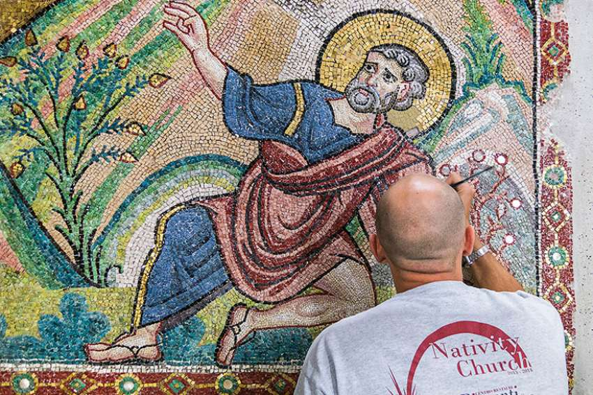 A restorer works on a wall of mosaic tiles in the Church of the Nativity in Bethlehem.