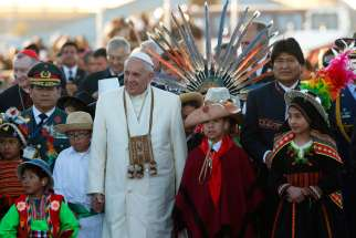 Pope Francis walks with Bolivian President Evo Morales and children in traditional dress as he arrives at El Alto International Airport in La Paz, Bolivia, July 8. The airport is over 4000 metres above sea level.