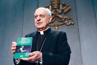 "Cardinal Lorenzo Baldisseri, secretary-general of the Synod of Bishops, holds Pope Francis' apostolic exhortation, ""Christus Vivit"" (Christ Lives), during a news conference April 2."