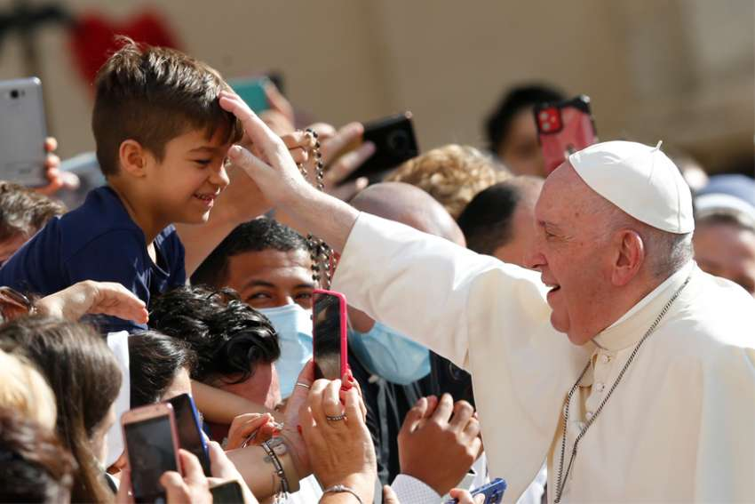 Pope Francis greets a boy as he arrives to lead his general audience in the San Damaso courtyard at the Vatican Sept. 9, 2020.