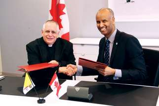 ICMC general secretary Msgr. Bob Vitillo and Canada's Immigration Minister Ahmed Hussen shake hands after renewing a commitment by the Canadian government to help fund the Catholic migration agency.