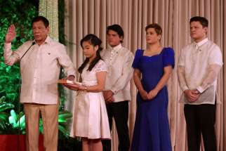 President Rodrigo Duterte takes the oath as his daughter Veronica holds the Bible during his presidential inauguration at the Malacanang Palace in Manila, Philippines. Duterte was sworn in as the 16th president of the Philippines.