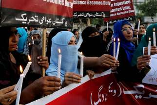 People hold candles during a March 29, 2016 gathering to mourn the victims of suicide bomb attack in Lahore, Pakistan.