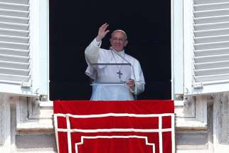 Pope Francis waves as he leads the Angelus from his studio overlooking St. Peter's Square at the Vatican April 23.