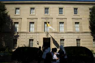 People are seen outside the Vatican Embassy, or apostolic nunciature, in Washington in 2014. A member of the Vatican diplomatic corps serving in Washington has been recalled to the Vatican where he is involved in a criminal investigation involving child pornography, the Vatican said.