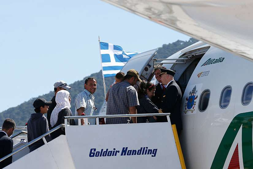 Refugees board Pope Francis' flight to Rome at the international airport in Mytilene on the island of Lesbos, Greece, April 16, 2016. The pope brought 12 refugees to Italy aboard his flight.