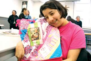 Gillian cuddles up to a blanket featuring a photo of her father, who passed away seven years ago, at a unique program for low-income or marginalized women grieving the loss of a loved one